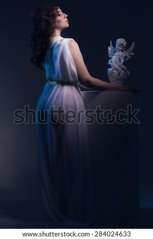 Beautiful Woman Wearing White Greek Toga in a dark antique interior - stock photo