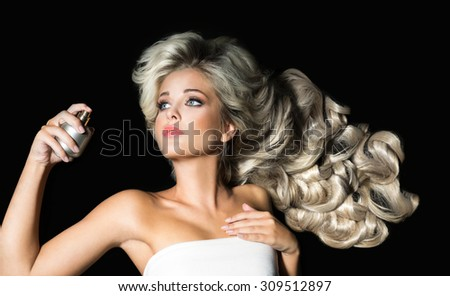 Beautiful woman with a bottle of perfume on the black background - stock photo