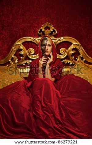 Beautiful woman with a carnival mask sitting in bed - stock photo