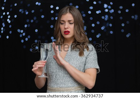 Beautiful woman with a glass of champagne on a black background with bokeh - stock photo
