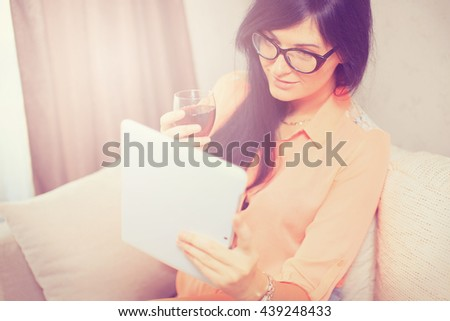 Beautiful woman  with a glass of wine, using tablet sitting on sofa at home - stock photo