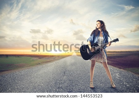 beautiful woman with a guitar on a deserted road - stock photo