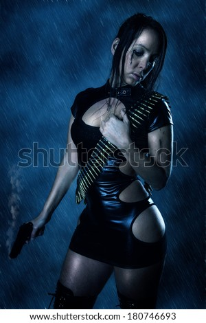Beautiful woman with a gun in the rain - stock photo
