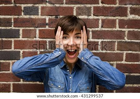 Beautiful woman with a happy expression in front of a brick wall - stock photo