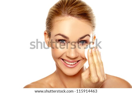 Beautiful woman with a lovely smile cleansing her face using a large cotton pad in a skincare and beauty concept isolated on white - stock photo