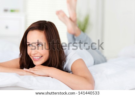 Beautiful woman with a lovely smile lying relaxing on her bed lying on her stomach facing the camera - stock photo