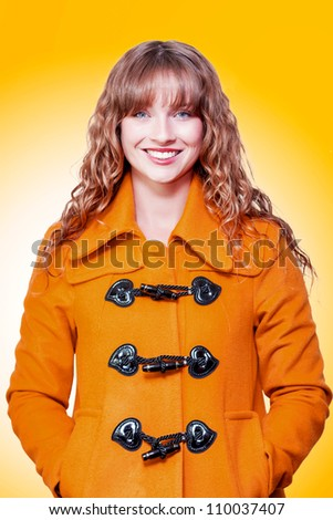 Beautiful woman with a lovely wide friendly smile and wavy blonde hair posing in an orange winter coat on an orange studio background with gradient colour - stock photo