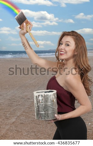 Beautiful woman with a paintbrush and paint can painting a rainbow - stock photo