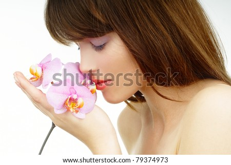 beautiful woman with a pink orchid on her naked arm - stock photo