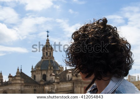 Beautiful woman with a sky with clouds and a church background - stock photo