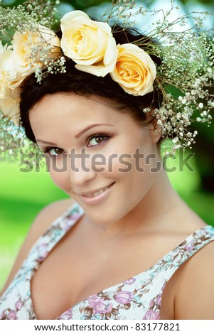 Beautiful woman with a wreath of roses on her head - stock photo