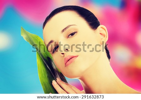 Beautiful woman with artistic make up and bamboo leaves - stock photo