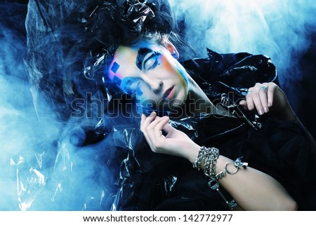 Beautiful woman with artistic make-up over smoke background - stock photo
