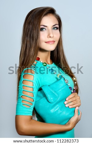 Beautiful woman with bag and colorful beads - stock photo