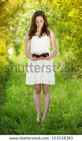 Beautiful woman with Bible is in sunny nature - stock photo