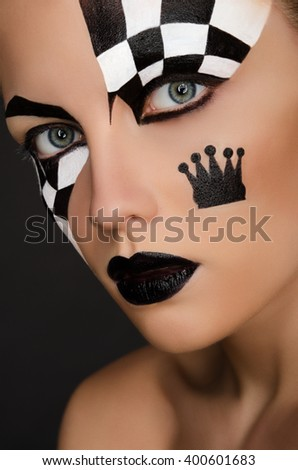 beautiful woman with black and white face art on black background - stock photo