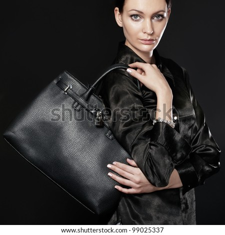 Beautiful woman with black bag - stock photo