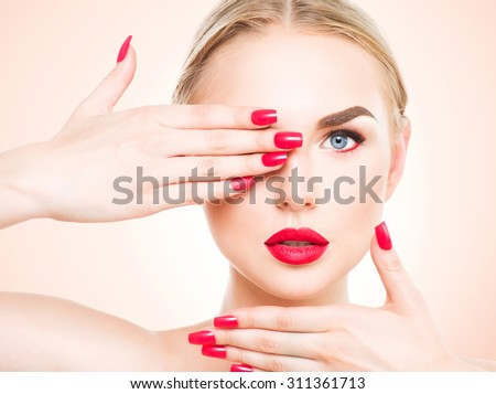 Beautiful woman with blond hair. Fashion model with red lipstick and red nails. Portrait of glamour girl with bright makeup. Beauty female face. Perfect skin and make up. Red lips and nail polish - stock photo