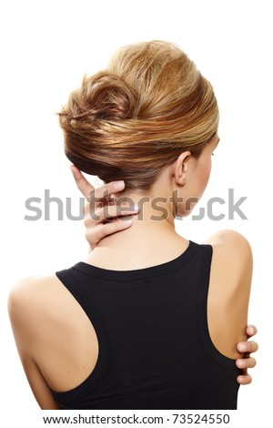 beautiful woman with blond hair in french roll wearing little black dress touching her neck view from the back on white - stock photo