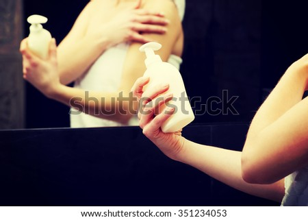 Beautiful woman with body lotion in bathroom. - stock photo