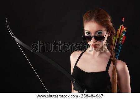 beautiful woman with bow in hand on black background - stock photo