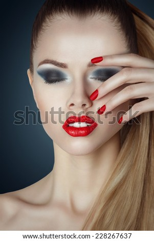 beautiful woman with bright glamour make-up. Red lips and nails. Blonde hair. Clean skin. - stock photo