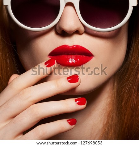 Beautiful woman with bright make-up and sunglasses - stock photo