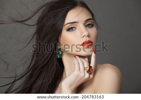 Beautiful woman with bright makeup and long brown hair wearing fine jewelry - stock photo