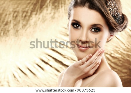 Beautiful woman with brooch in hair over golden background - stock photo