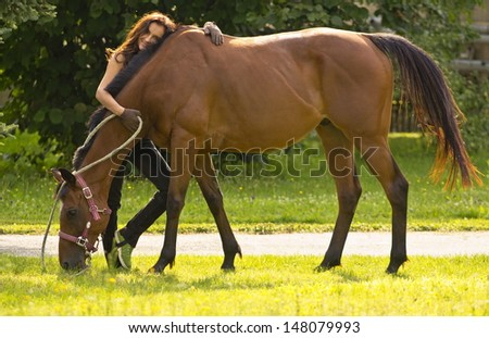 Beautiful woman with brown horse. - stock photo
