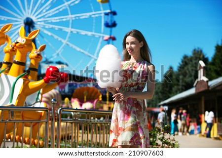 beautiful woman with candy floss in the park - stock photo