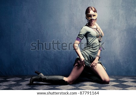 beautiful woman with carnival mask posing on floor,  full body shot, indoor shot - stock photo