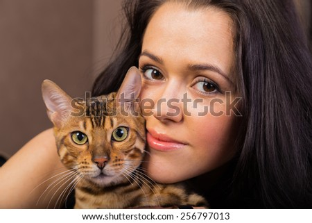 Beautiful woman with cat portrait. Brunette with bengal cat close-up. - stock photo