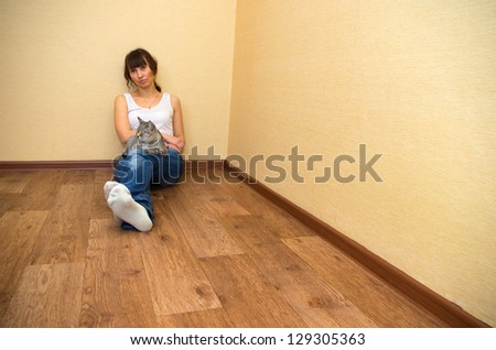 Beautiful woman with cat sitting on the floor - stock photo