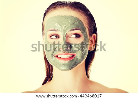 Beautiful woman with clay facial mask - stock photo