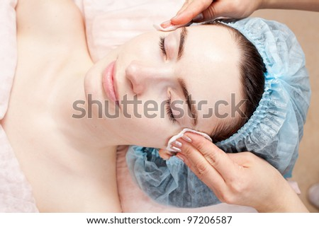 Beautiful woman with clear skin getting beauty treatment of her face at salon - stock photo