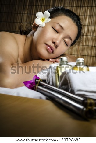 Beautiful woman with closed eyes relaxing at spa and massage - stock photo