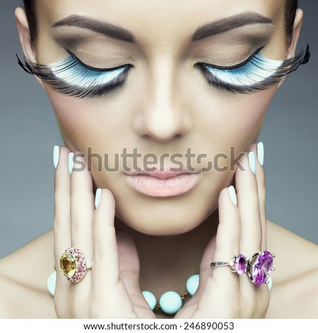 Beautiful woman with color eyelashes. Makeup and manicure. Jewelry.Closeup - stock photo