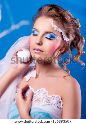 beautiful woman with creative bright makeup in the studio (winter topic) - stock photo