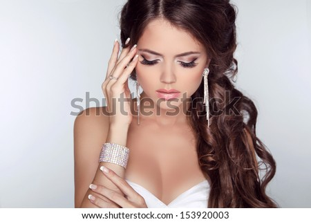 Beautiful woman with curly hair and evening make-up isolated on grey background. Jewelry and Beauty. Fashion photo - stock photo