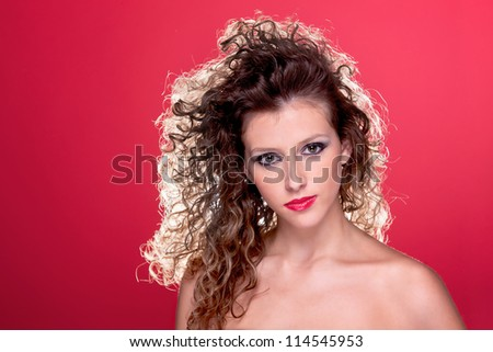 beautiful woman with curly hair, with light from behind, on red, studio shot - stock photo