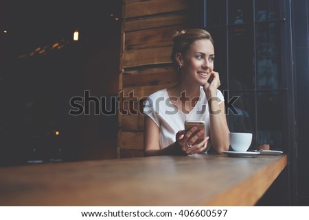 Beautiful woman with cute smile holding smart phone while sitting in cafe bar during her recreation time, happy European female using cell telephone while relaxing in modern coffee shop after work day - stock photo