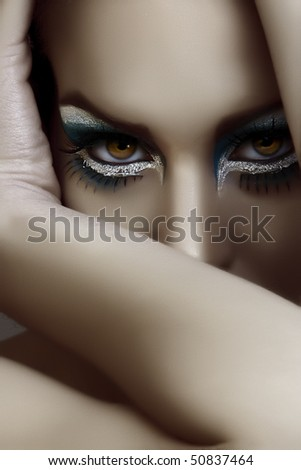beautiful woman with dark goth make-up covering her face with an arm - stock photo