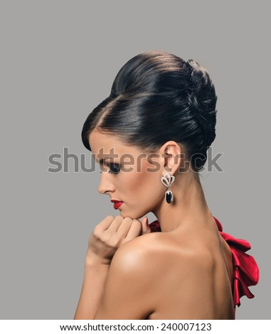 beautiful woman with dark tanned skin and black hair in fashion hairstyle and earrings. - stock photo
