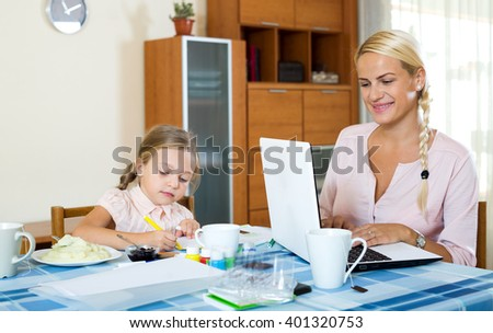 Beautiful woman with daughter working from home using laptop - stock photo