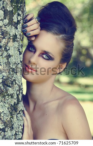 beautiful woman with dramatic eye make-up, gray manicure & beehive hairstyle outdoors next to the tree with natural bokeh effect, split tone colour for fashion look. - stock photo