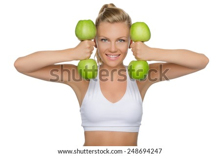 Beautiful woman with dumbbells of green apples isolated on white - stock photo