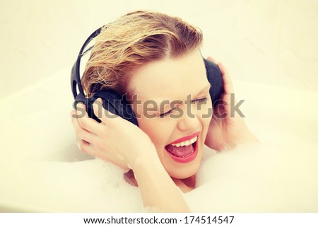Beautiful woman with earphones in the bath. Relax in bathroom. - stock photo