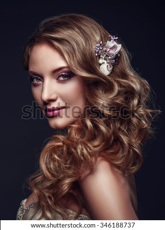 Beautiful woman with evening make-up and long wavy hair. Bright makeup. Fashion photoshoot. Bride half-turned. Studio shoot on a grey background.  - stock photo