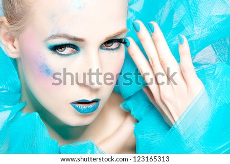 beautiful woman with extreme colorful make up in turquoise closeup - stock photo